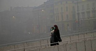 Women wearing masks walk as smog blankets Sarajevo, Bosnia and Herzegovina December 23, 2015. With severe air pollution affecting the city nestled among the mountains, the authorities have declared the first level of preparedness, advising the segment of the population that is at health risk to reduce movement in the mornings and evenings, appealing to drivers to use motor vehicles less and ordering heating utilities to lower the emission of harmful gases. REUTERS/Dado Ruvic